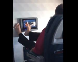 Mujer capta a un pasajero manipular una pantalla táctil con su pie descalzo al interior de un avión