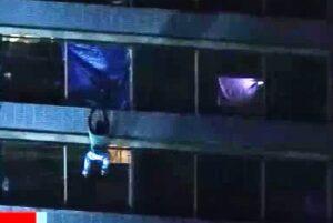 Un hombre desciende de un edificio en llamas por las ventanas