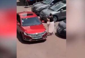 Mujer usa cinta métrica para cerciorarse que sí cabe su auto en un estacionamiento