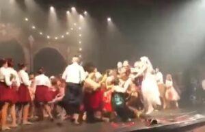 Bailarines brincan sobre el escenario de un teatro y lo derriban