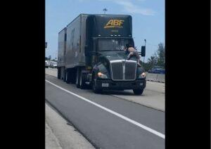 Un hombre semidesnudo viaja sobre el capó de un camión en una carretera de Florida
